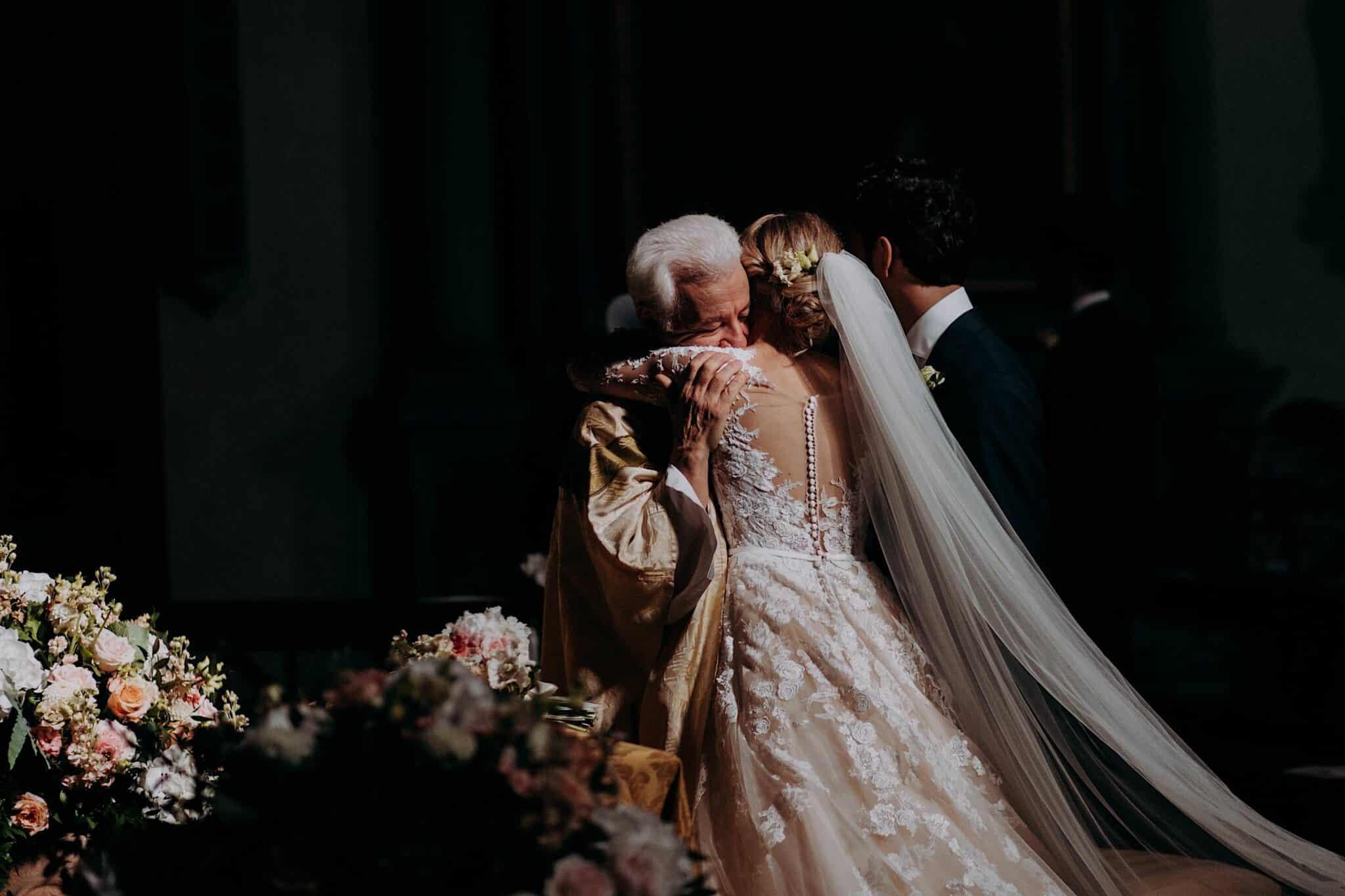 abbracci tra il parroco e gli sposi